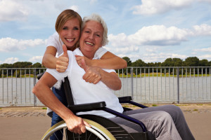 Happy disabled woman and nurse holding their thumbs