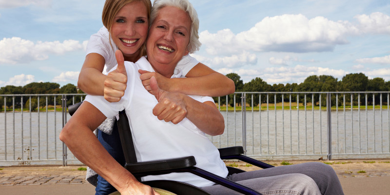 Happy disabled woman and nurse holding their thumbs up